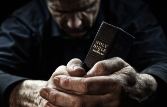 A Man praying holding a Holy Bible.